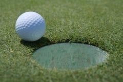Pelota de golf en la taza Fotografía de archivo libre de regalías