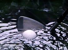 Pelota de golf en un hazzard del agua con el club del hierro Foto de archivo libre de regalías