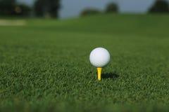 Pelota de golf en una camiseta Foto de archivo libre de regalías