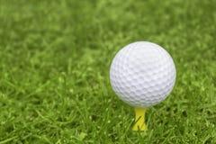 Pelota de golf en una camiseta amarilla con un fondo borroso para el balneario de la copia Foto de archivo
