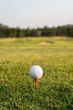 Pelota de golf en una camiseta contra el campo de golf Imagen de archivo