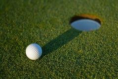 Pelota de golf encendido al lado del agujero 2 imagenes de archivo