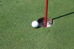 Pelota de golf por el agujero Fotografía de archivo