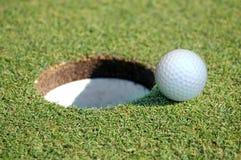 Pelota de golf que entra en el agujero Imagen de archivo