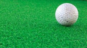 Pelota de golf sobre el vidrio y el fondo de la falta de definición Imagen de archivo