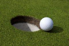 Pelota de golf y agujero Imagenes de archivo