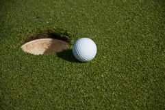 Pelota de golf y agujero Imágenes de archivo libres de regalías