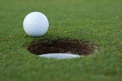 Pelota de golf y agujero fotografía de archivo