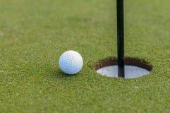 Pelota de golf y agujero Fotos de archivo