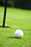 Pelota de golf y agujero Fotos de archivo libres de regalías
