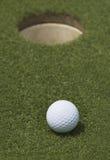 Pelota de golf y agujero Foto de archivo