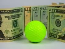 Pelota de golf y billetes de dólar verdes de neón imagenes de archivo