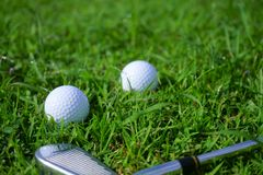 Pelota de golf y camiseta en fondo verde del curso del golf foto de archivo