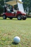 Pelota de golf y cochecillo Imagen de archivo