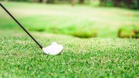 Pelota de golf y conductor en el campo de prácticas Foto de archivo