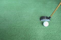 Pelota de golf y putter en hierba verde Imagenes de archivo