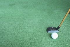 Pelota de golf y putter en hierba verde Fotografía de archivo