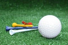 Pelota de golf y tes imagen de archivo