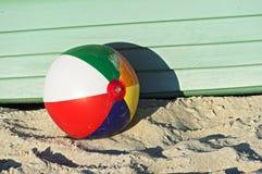 Pelota de playa colorida delante de un barco verde Imagen de archivo libre de regalías