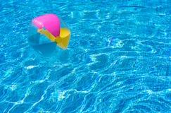 Pelota de playa colorida en agua de la piscina Imagen de archivo libre de regalías