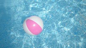 Pelota de playa colorida en piscina metrajes