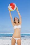 Pelota de playa de cogida sonriente de la mujer delgada Fotografía de archivo