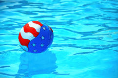 Pelota de playa de la bandera en piscina Fotos de archivo libres de regalías