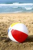 Pelota de playa en arena Imagenes de archivo