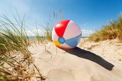 Pelota de playa en duna de arena Imagen de archivo libre de regalías