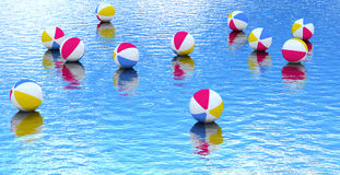Pelota de playa que flota en el agua azul fotografía de archivo