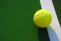 Pelota de tenis amarilla en la línea lateral blanca Fotografía de archivo