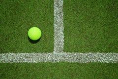Pelota de tenis cerca de la línea en la corte de hierba del tenis buena para el backgro Foto de archivo