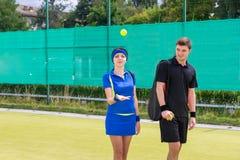 Pelota de tenis del jugador de tenis de la mujer que lanza cerca de su socio en el A.C. Imagen de archivo libre de regalías