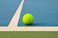 Pelota de tenis en corte azul Fotografía de archivo