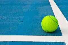Pelota de tenis en corte azul Foto de archivo libre de regalías