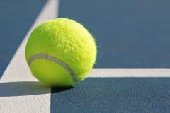 Pelota de tenis en corte azul Foto de archivo