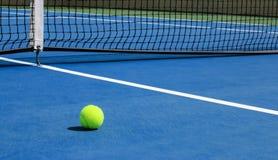 Pelota de tenis en corte azul con la red en fondo imagen de archivo
