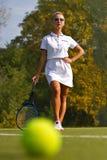 Pelota de tenis en el campo de tenis con el jugador en el fondo Imagen de archivo libre de regalías