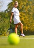 Pelota de tenis en el campo de tenis con el jugador en el fondo Foto de archivo libre de regalías