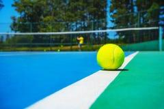 Pelota de tenis en la línea blanca de la corte en corte verde azul moderna dura con el jugador, red, bolas, árboles en el fondo imágenes de archivo libres de regalías