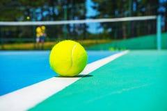 Pelota de tenis en la línea blanca de la corte en corte verde azul moderna dura con el jugador, red, bolas, árboles en el fondo imagen de archivo libre de regalías