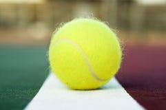Pelota de tenis en la línea de fondo de la corte Imagen de archivo libre de regalías