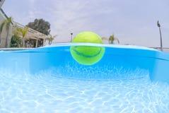 Pelota de tenis en piscina Fotos de archivo