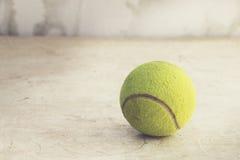 Pelota de tenis en piso de madera Imagen de archivo libre de regalías
