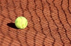 Pelota de tenis en una corte de arcilla del tenis con la sombra neta Imagen de archivo