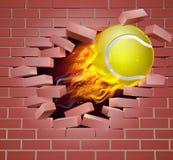 Pelota de tenis llameante que se rompe a través de la pared de ladrillo Foto de archivo libre de regalías