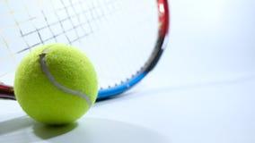 Pelota de tenis y estafa sobre el fondo blanco Fotografía de archivo