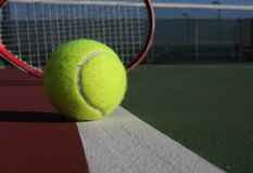 Pelota de tenis y raqueta en corte Fotos de archivo