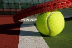 Pelota de tenis y raqueta en una corte Imágenes de archivo libres de regalías