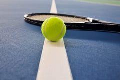 Pelota de tenis y raqueta en una línea de la corte Fotografía de archivo